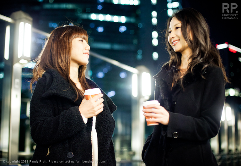 Two young Japanese women drinking coffee and hanging out at night in Tokyo.